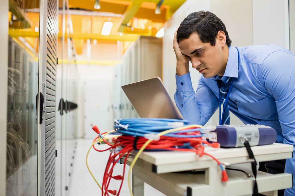 Stressed technician using laptop in server room