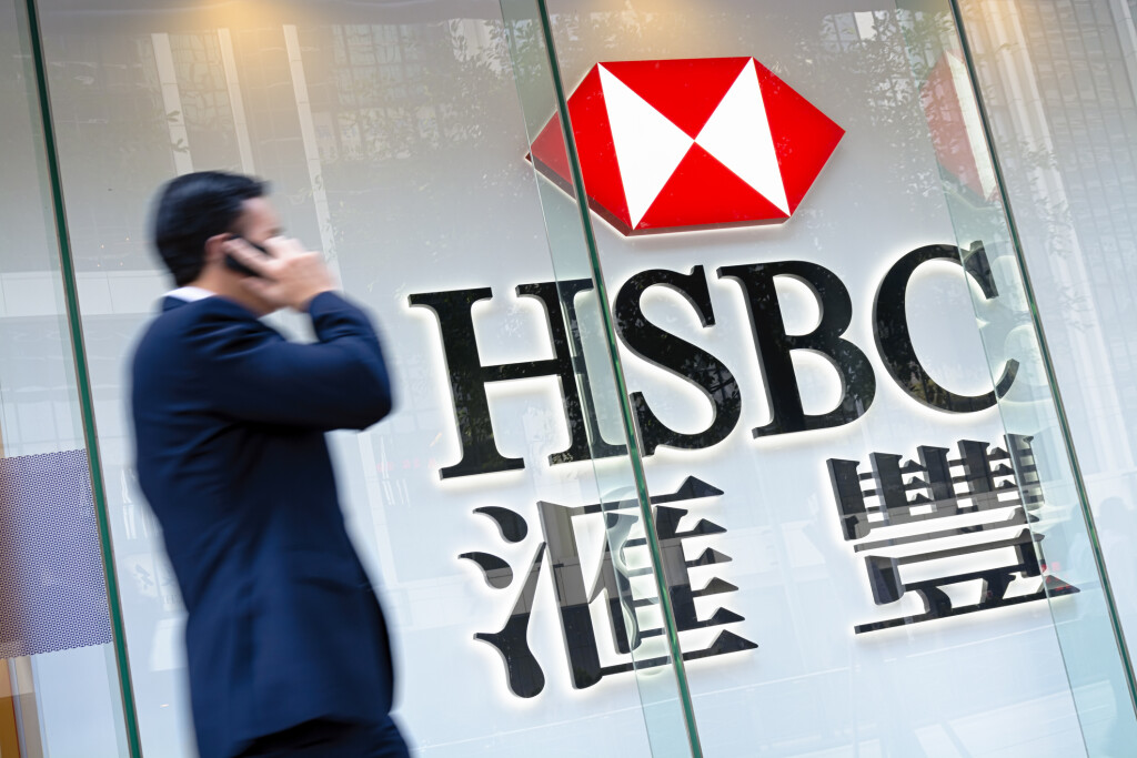 Hong Kong, Hong Kong SAR -November 17, 2014: Motion blured business man passing by an HSBC Bank sign in Hong Kong. HSBC Holdings plc is the world's third largest bank by assets.